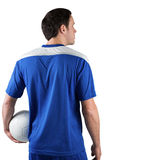 Football player in blue holding ball Stock Image