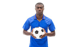 Football player in blue holding the ball Royalty Free Stock Images