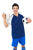 Football player in blue holding winners cup and ball Royalty Free Stock Images
