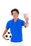 Football player in blue holding winners cup Stock Photo