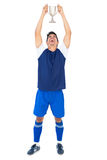 Football player in blue holding winners cup Royalty Free Stock Photo