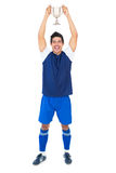 Football player in blue holding winners cup Royalty Free Stock Photos