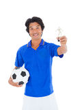 Football player in blue holding winners trophy Royalty Free Stock Images