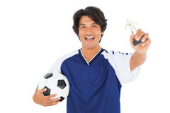 Football player in blue holding winners trophy Stock Image