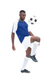Football player in blue jersey controlling ball. On white background Royalty Free Stock Photography