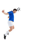 Football player in blue jersey heading ball Royalty Free Stock Image