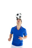 Football player in blue jersey heading ball Stock Photo