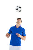 Football player in blue jersey heading ball Royalty Free Stock Images