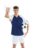 Football player in blue jersey holding winners cup Royalty Free Stock Photo