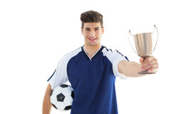 Football player in blue jersey holding winners cup Royalty Free Stock Photography