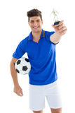 Football player in blue jersey holding winners trophy Stock Photos