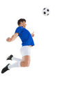 Football player in blue jersey jumping to ball Royalty Free Stock Photography