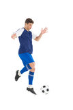 Football player in blue jersey kicking ball Stock Images