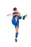 Football player in blue jersey kicking. On white background Royalty Free Stock Photos
