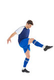 Football player in blue jersey kicking Stock Photos