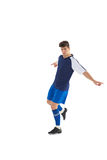 Football player in blue jersey kicking Royalty Free Stock Photography
