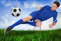 Football player in blue kicking the ball Royalty Free Stock Photos