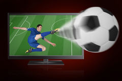 Football player in blue kicking ball out of tv Stock Image