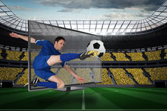 Football player in blue kicking ball out of tv Stock Photos
