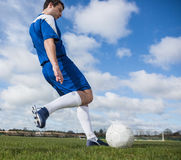 Football player in blue kicking the ball on pitch Royalty Free Stock Photography