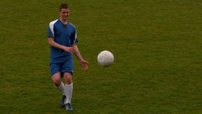 Football player in blue kicking the ball on pitch stock footage