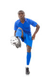 Football player in blue kicking ball Royalty Free Stock Photo