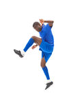 Football player in blue kicking and jumping Stock Photos