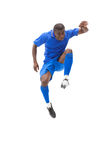 Football player in blue kicking and jumping Stock Images
