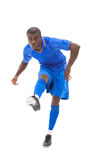 Football player in blue kicking Royalty Free Stock Image