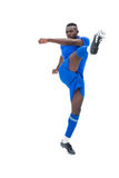 Football player in blue kicking Stock Photography
