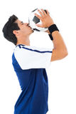 Football player in blue kissing ball Stock Photo