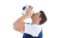 Football player in blue kissing the ball stock photo