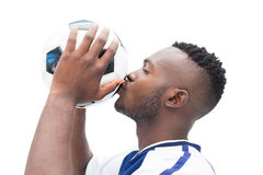 Football player in blue kissing ball Stock Photography