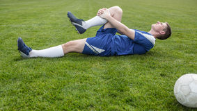 Football player in blue lying injured on the pitch Stock Photo