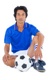 Football player in blue sitting with ball Royalty Free Stock Photos