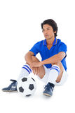 Football player in blue sitting with ball Stock Image