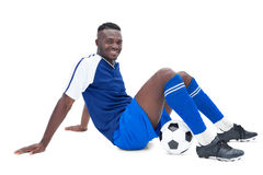 Football player in blue sitting with ball Royalty Free Stock Images