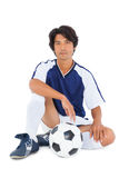Football player in blue sitting with ball Royalty Free Stock Photography