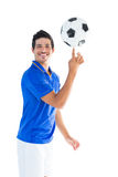 Football player in blue spinning ball Stock Photo