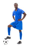 Football player in blue standing with the ball Royalty Free Stock Photography