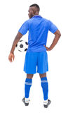 Football player in blue standing with ball Stock Photos