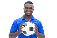 Football player in blue standing with the ball Stock Image