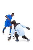 Football player in blue striking at keeper Stock Photo
