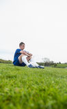 Football player in blue taking a break on the pitch Royalty Free Stock Photos