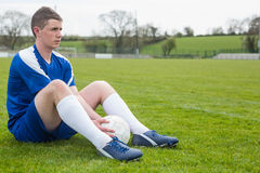 Football player in blue taking a break on the pitch Stock Photo