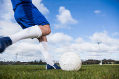 Football player in blue about to kick ball Stock Image
