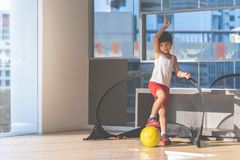Football player boy stepping on the ball in the room royalty free stock photography