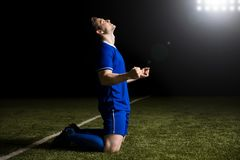 Football player cheering after scoring. Happy young soccer player celebrates after scoring a goal during match in stadium Royalty Free Stock Photography