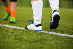 Football player crossing white line on the field. Football player crossing white line on the soccer field. training session befor final game Royalty Free Stock Image