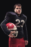 Football player on dark background Royalty Free Stock Photography